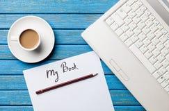 咖啡和纸与我的书题字在笔记本附近 免版税库存图片