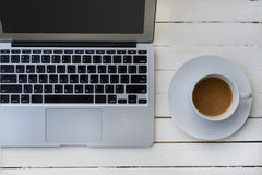 咖啡和膝上型计算机在木桌上 免版税图库摄影