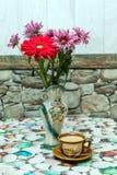 咖啡和花瓶有花的在桌上 免版税库存图片
