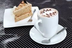 咖啡和蛋糕在圆点桌上 免版税库存图片