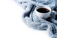 咖啡和被编织的毛线衣在白色桌上 免版税库存图片