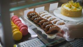 咖啡和酥皮点心酒吧 柜台 玻璃表面上点心被暴露 在右边多彩多姿的法国macarons 股票录像