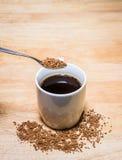 咖啡咖啡粒子和匙子在木桌上的 在粒子的焦点 库存照片