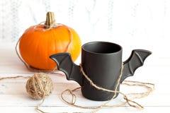 咖啡喜欢在包装在万圣夜的红色纸的一根棒 奶油被装载的饼干 玩具、南瓜和球毛线 图库摄影