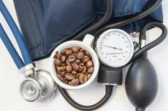 咖啡因和血压 小杯子用咖啡豆,象征咖啡因在血压计附近,电灯泡、袖口和听诊器t 免版税库存照片