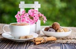咖啡在一木tabl的、花和甜点shekoladnye 免版税图库摄影