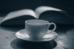 咖啡在一本开放书的背景的 库存图片