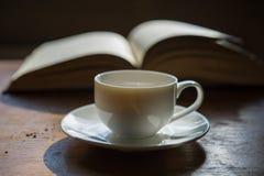 咖啡在一本开放书的背景的 免版税图库摄影