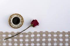咖啡在一根鞋带附近的与一朵红色玫瑰 库存照片