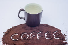 咖啡在与棕色杯子的咖啡渣拼写了 库存图片