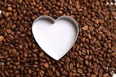 咖啡在咖啡豆背景自由空间的心脏白色 图库摄影