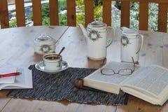 咖啡在大阳台的,放松与书 免版税库存图片
