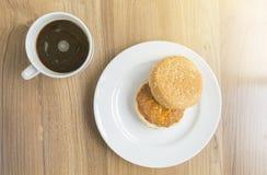咖啡在木桌上的和猪肉汉堡与阳光 免版税库存图片