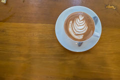 咖啡在木桌上的拿铁艺术 库存照片