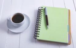 咖啡在木背景的笔记本笔 库存照片
