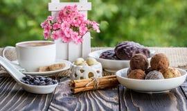 咖啡在木tabl的、花和甜点shekoladnye 免版税库存照片