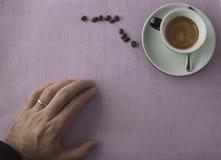 咖啡在桌上的用手和豆 免版税图库摄影