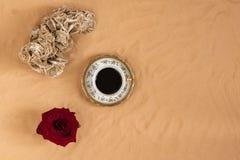 咖啡在沙子的与玫瑰 库存图片