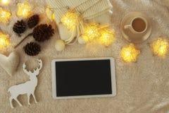 咖啡在片剂设备旁边的有在舒适和温暖的毛皮地毯的空的屏幕的 顶视图 库存照片