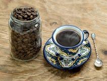 咖啡在瓶子的豆旁边 免版税库存照片