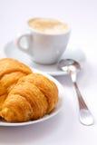 咖啡在茶碟的和新月形面包 免版税图库摄影