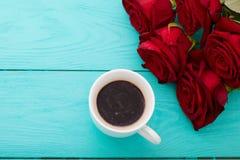 咖啡在蓝色木桌上的 顶视图 嘲笑 热的饮料 选择聚焦 红色唤醒花束 华伦泰母亲节 图库摄影