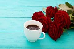 咖啡在蓝色木桌上的 顶视图 嘲笑 热的饮料 选择聚焦 红色唤醒花束 华伦泰母亲节 免版税库存照片