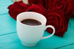 咖啡在蓝色木桌上的 顶视图 嘲笑 热的饮料 选择聚焦 红色唤醒花束 图库摄影