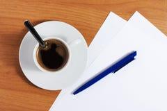 咖啡在表的与纸张和笔 免版税图库摄影