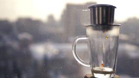 咖啡在都市风景的背景滴下在杯子的下落窗口外 在越南语的酿造咖啡 库存照片