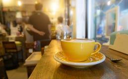 咖啡在黄色咖啡杯和在木背景 图库摄影