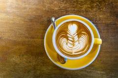 咖啡在黄色咖啡杯和在木背景 免版税库存图片