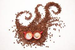 咖啡妖怪、咖啡豆和2个杯子浓咖啡 免版税库存图片