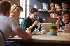 咖啡店内部与使用数字式设备的顾客的 免版税图库摄影