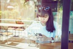 咖啡店的亚裔妇女接触智能手机屏幕,使用传送信息到朋友社会媒介应用 库存图片