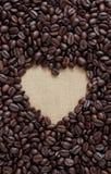 咖啡恋人标志,堆在心脏形状的棕色咖啡豆 免版税图库摄影
