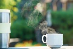 咖啡或茶与蒸汽和热水瓶在自然摘要 免版税库存图片