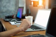 咖啡手中人民与计算机,巧妙的电话o一起使用 免版税库存照片