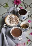 咖啡拿铁、浓咖啡、巧克力热饮和点心在一把古色古香的桌和银色盘子和老匙子的背景 库存照片