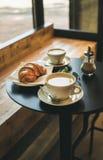 咖啡拿铁、热奶咖啡和新月形面包在小桌上在咖啡馆 免版税库存图片
