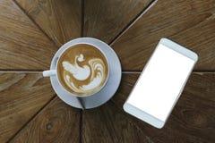 咖啡拿铁在白色陶瓷杯子的艺术样式顶视图除有空白的白色屏幕的白色巧妙的电话以外 库存图片