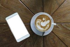 咖啡拿铁在白色陶瓷杯子的艺术样式顶视图除有空白的白色屏幕的白色巧妙的电话以外 免版税图库摄影