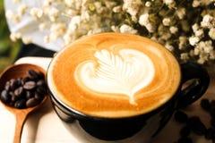 咖啡拿铁牛奶奶油花木匙子咖啡豆背景木头 免版税库存照片