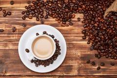 咖啡拿铁用在一张木桌上的咖啡豆 库存图片