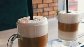 咖啡拿铁用牛奶和空气起泡沫,并且黑秸杆在桌上的一块透明特别玻璃站立在时髦的咖啡馆 股票录像