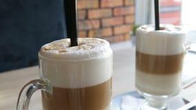 咖啡拿铁用牛奶和空气起泡沫,并且黑秸杆在桌上的一块透明特别玻璃站立在时髦的咖啡馆 影视素材