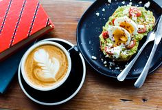 咖啡拿铁艺术用鲕梨多士和鸡蛋 免版税库存图片