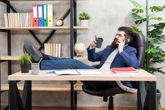 咖啡放松的断裂 人有胡子的商人举行杯子和智能手机 咖啡是成功的交涉承诺  库存图片