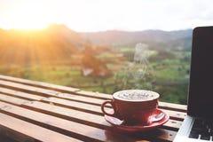 咖啡早晨和膝上型计算机在木桌上与美丽的mountai 免版税库存图片