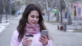 咖啡时间,夫人在有智能手机的互联网有塑料杯子手中特写镜头的坐街道 股票视频